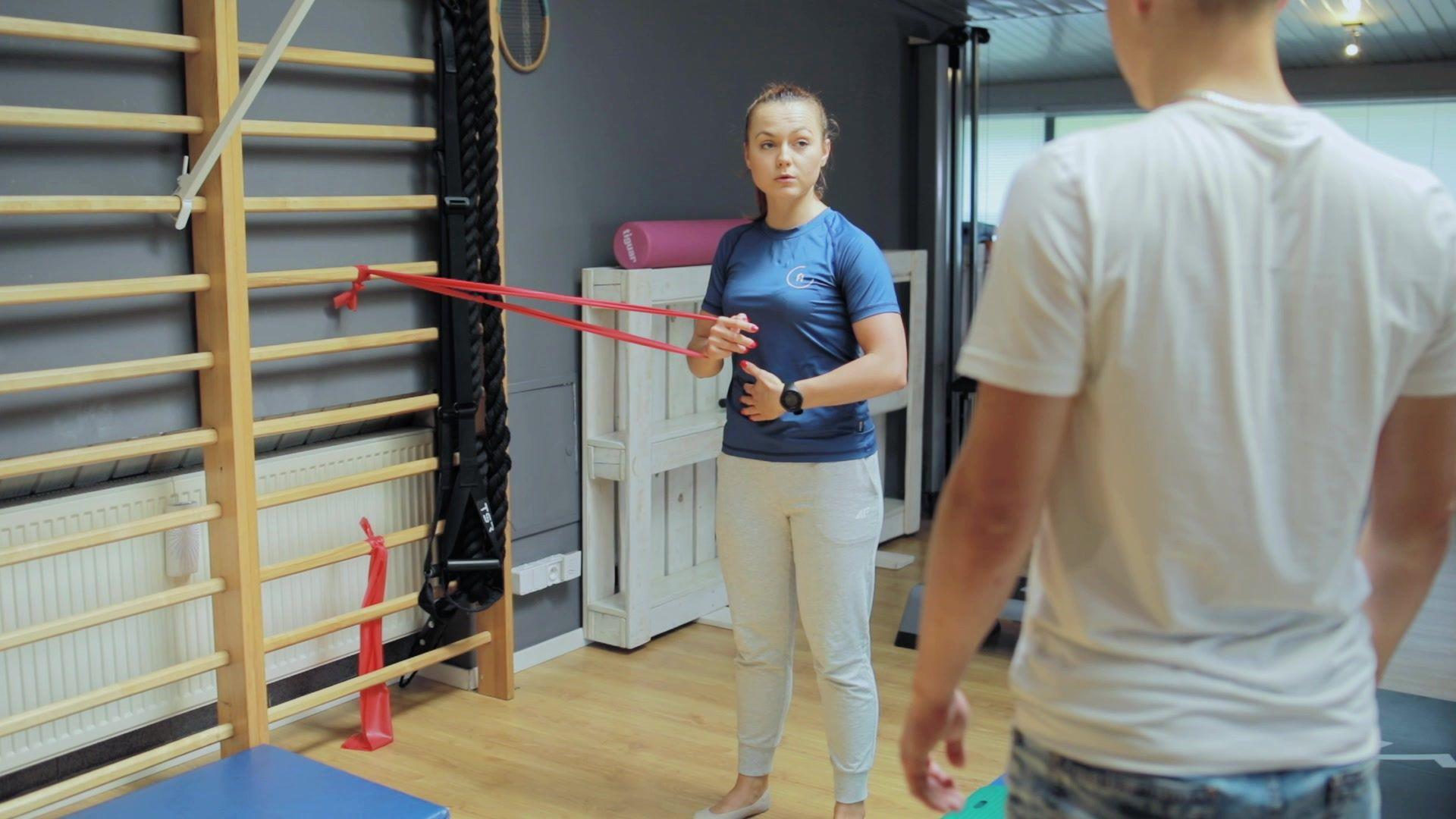 fizjoterapeuta pokazuje prawidłowe wykonanie cwiczenia rehabilitacyjnego